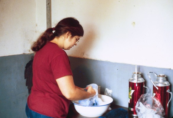 Washing a sweater in an enamel basin in our kitchen. I was too shocked to take pictures the night we arrived. Gauss took this photo a few weeks later. Notice the big enameled Thermoses. They were everywhere.