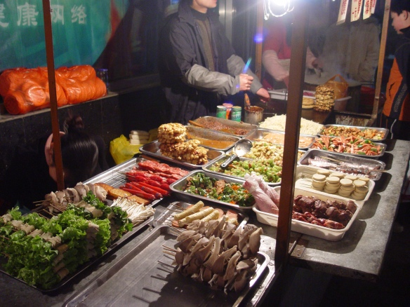 Meats, vegetables, and tofu ready to be skewered and grilled at a sidewalk eatery