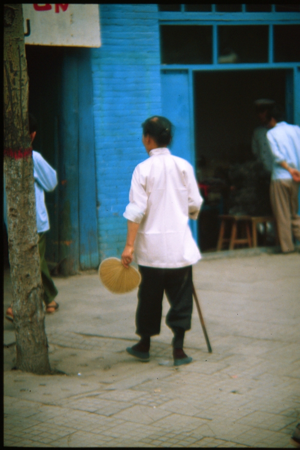 An elderly woman with bound feet on a city sidewalk in Xi'an, 1982. © Patti Isaacs